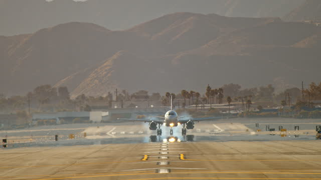ws extreme long lens view of passenger jet touching down on airport runway against background of palm trees and desert mountain range as skidding aircraft tires eject white smoke upon touchdown - distorted stock videos & royalty-free footage