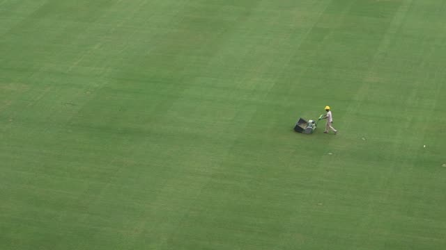 extreme long shot a member of stadium personnel walking across the pitch with a lawn mower a tragic accident at arena de sao paulo led to the death... - lawn stock videos & royalty-free footage