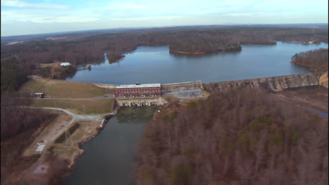 extreme long shot aerial , a road leads across a man made dam. / charlotte, north carolina, usa - charlotte north carolina stock videos & royalty-free footage