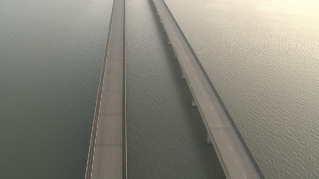 extreme long shot aerial push-in - the escambia bay bridge spans rippling water. / florida, usa - freie straße stock-videos und b-roll-filmmaterial