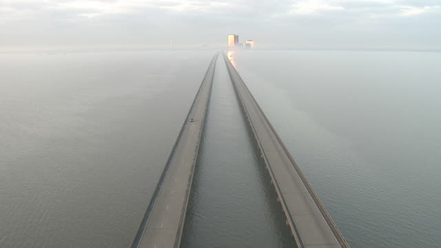 Extreme Long Shot aerial push-in - The Escambia Bay Bridge stretches toward skyscrapers on the horizon. / Florida, USA