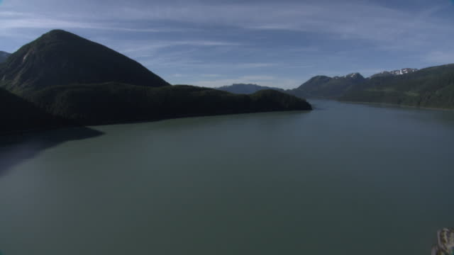 "vídeos de stock e filmes b-roll de ""extreme long shot aerial push-in-a wide, calm river flows past forested alaskan mountains. / alaska, usa"" - alasca"