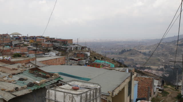 vídeos de stock e filmes b-roll de extreme long shot from a high angle over the rooftops of the huts showing the cityscape of the slum situated on the mountain camera movement pan from... - bairro de lata
