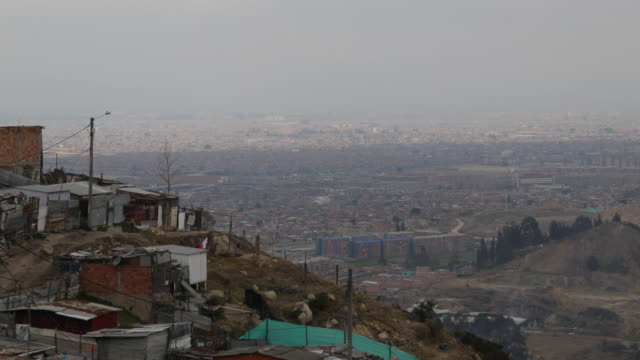 vídeos de stock e filmes b-roll de extreme long shot from a high angle over the rooftops of the huts showing the cityscape of the slum situated on the mountain camera movement tilt... - bairro de lata