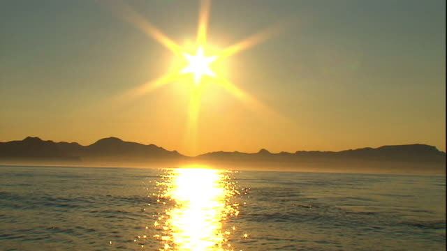 extreme long shot hand-held - the ocean reflects a stream of light from the sun. - seascape stock videos & royalty-free footage