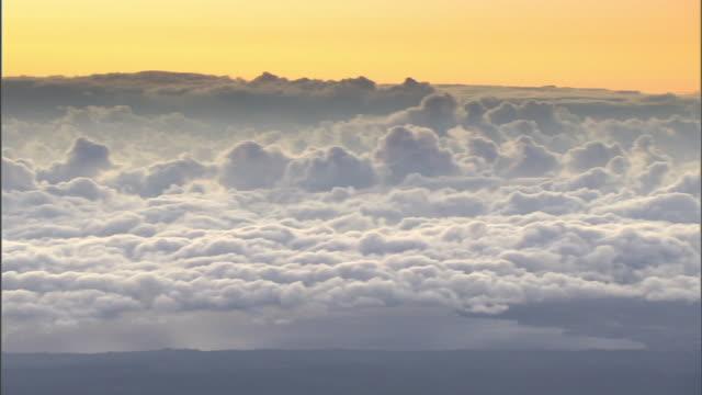 Extreme Long Shot pan-left - A yellow sky glows behind a sea of clouds at Mauna Kea, Hawaii, at sunset. / Mauna Kea, Hawaii, USA