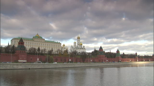 Extreme Long Shot pan-left - Storm clouds loom over the Grand Kremlin Palace beyond the Moskva River in Moscow, Russia. / Moscow, Russian Federation