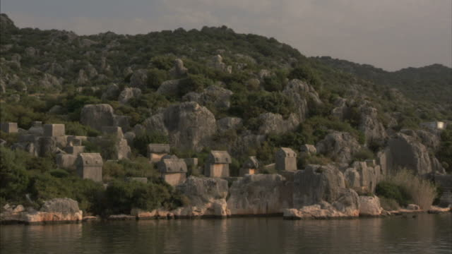 extreme long shot pan-left tracking-right - stone huts and carvings in ancient cliffs constitute a rocky shoreline on the mediterranean. / turkey - mediterranean culture stock videos & royalty-free footage