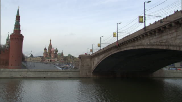 extreme long shot pan-left - traffic moves past a bridge and river in moscow. / moscow, russian federation - st. basil's cathedral stock videos and b-roll footage