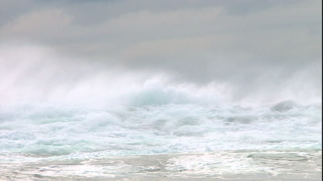extreme long shot pan-left - wind blows mist off powerful waves. - powerful stock videos and b-roll footage