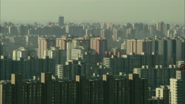 Extreme Long Shot pan-right - A multitude of high-rises fill the smoggy city of Beijing./Beijing, China
