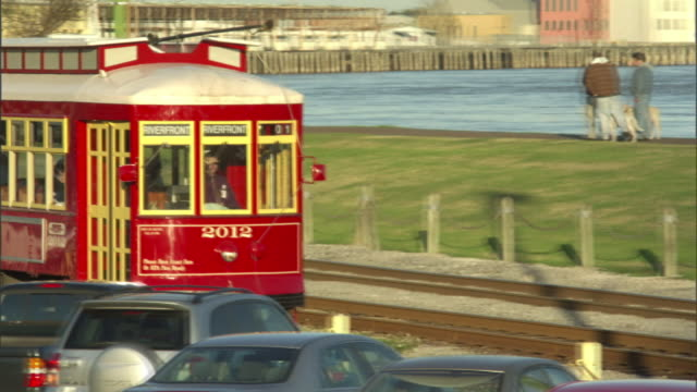 extreme long shot pan-right - a trolley zips past a waterfront in new orleans. / new orleans, louisiana, usa - trolley bus stock videos & royalty-free footage