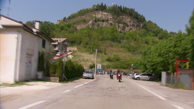 extreme long shot push-out - a motorcyclist drives around a sharp curves. / italy - 乗物後部から見た視点点の映像素材/bロール