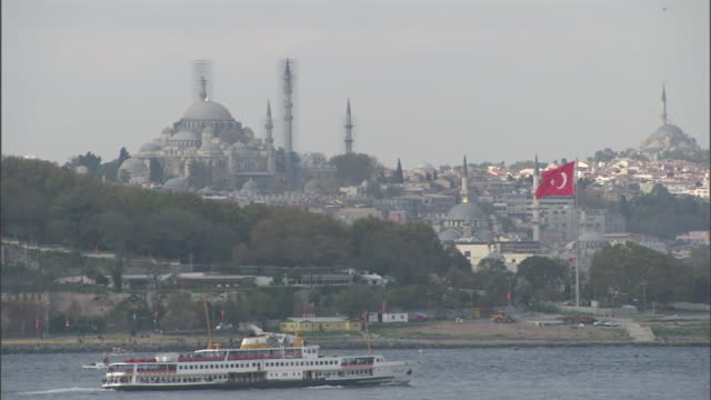 extreme long shot static - a ferry boat passes the blue mosque. / istanbul, turkey - イスタンブール 金角湾点の映像素材/bロール