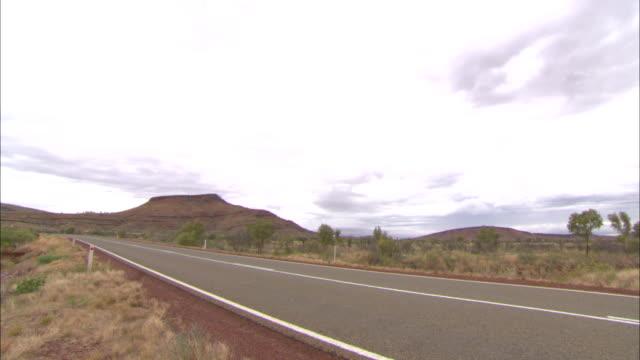 vídeos y material grabado en eventos de stock de extreme long shot static - a highway cuts through a field near a rock formation in the karijini national park. / australia - carretera vacía