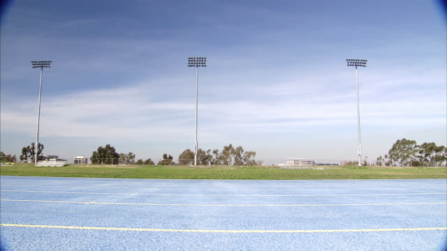 Extreme Long Shot static - An athlete runs across a track. / California