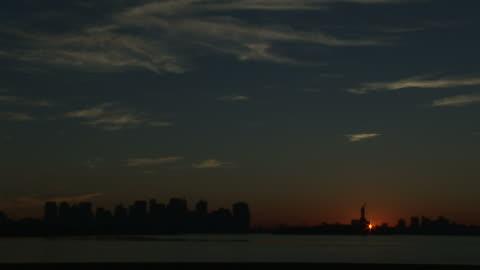 vídeos y material grabado en eventos de stock de extreme long shot  static - an early morning sun silhouettes the new york city skyline. /  new york city - statue of liberty new york city