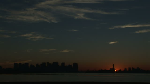 extreme long shot  static - an early morning sun silhouettes the new york city skyline. /  new york city - statue of liberty new york city video stock e b–roll
