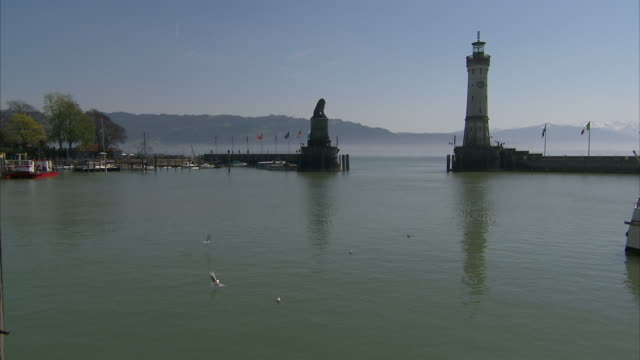 extreme long shot static - seagulls fly over a harbor near a lighthouse and stone monument. / lindau, germany - medium group of animals stock videos & royalty-free footage