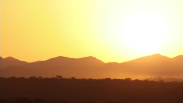 Extreme Long Shot static - The sun rises behind a mountain range in Benin. / Benin