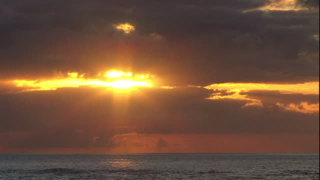 extreme long shot static - the sun sets over the ocean in hawaii. / hawaii, usa - seascape stock videos & royalty-free footage