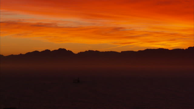 Extreme Long Shot static - Vibrant orange clouds glow above a mountainous coast. / South Africa