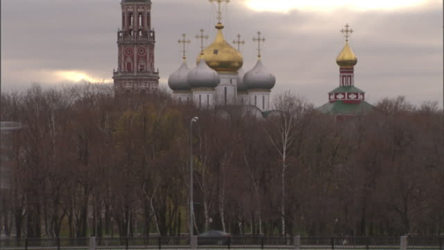 extreme long shot tilt-up - heavy traffic passes st. basil's cathedral in moscow. / moscow, russian federation - onion dome stock videos and b-roll footage