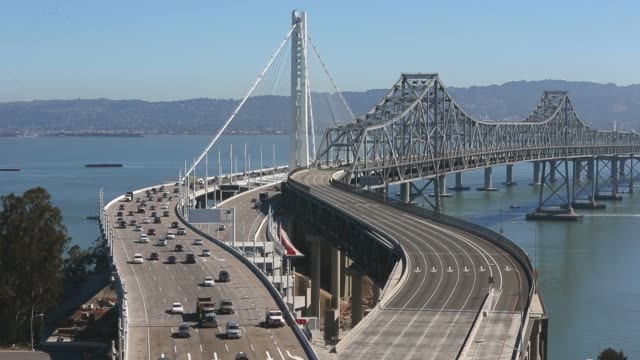 vídeos de stock e filmes b-roll de extreme long shot, traffic flows across the new eastern span of the san francisco oakland bay bridge as the old eastern span sits empty on the... - san francisco oakland bay bridge