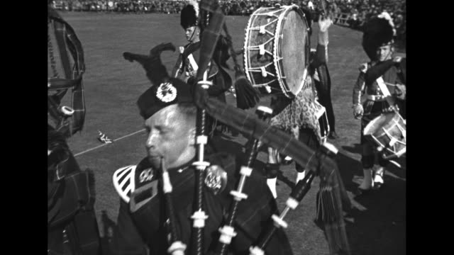 extreme long view of game grounds / band marches in kilts / medium view of bagpipers playing / a drummer beats on drum / soldiers march / royal... - highland games stock videos & royalty-free footage