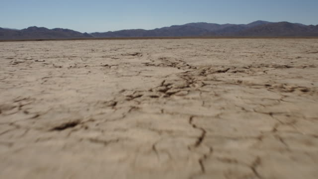 vidéos et rushes de extreme low angle track across dry lake bed - land