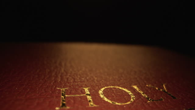"extreme macro close-up moving slider reveal shot shot of gold text title ""holy bible"" on the cover texture pattern book of the word of god on a dark background with unique lighting - book cover stock videos & royalty-free footage"