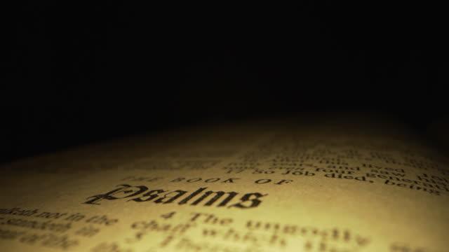 ユニークな照明を持つ暗い背景に神の言葉のための赤い文字とキングジェームズ翻訳のキリスト教聖書の詩篇のタイトルに焦点を当てて聖書の極端なマクロクローズアップ移動スライダーシ� - 聖書点の映像素材/bロール