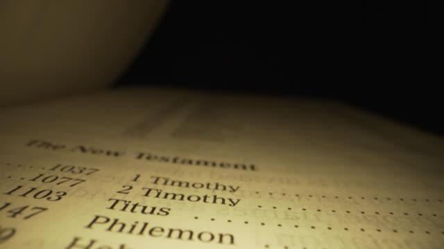 極端なマクロクローズアップは、ユニークな照明を持つ暗い背景に神の言葉のための赤い文字でキングジェームズ翻訳でキリスト教の聖書の聖書新約聖書インデックスブックの移動スライダ� - 新約聖書点の映像素材/bロール