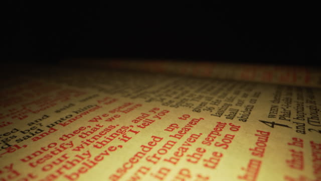 extreme macro close-up moving slider shot of scripture st. john words in the christian bible in king james translation with red letters for the word of god on a dark background with unique lighting - bible stock videos & royalty-free footage