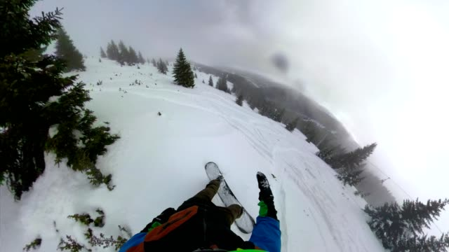 extreme man riding a snowboard through a snow covered mountain forest - work helmet stock videos & royalty-free footage