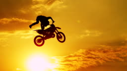 SLOW MOTION CLOSEUP: Extreme motocross biker jumping freestyle trick at sunset