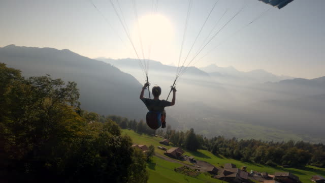 vidéos et rushes de extreme paraglider flying in swiss alps at sunny day - parapente