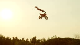 SLOW MOTION: Extreme pro motocross biker jumping over kicker performing a trick at beautiful golden sunset