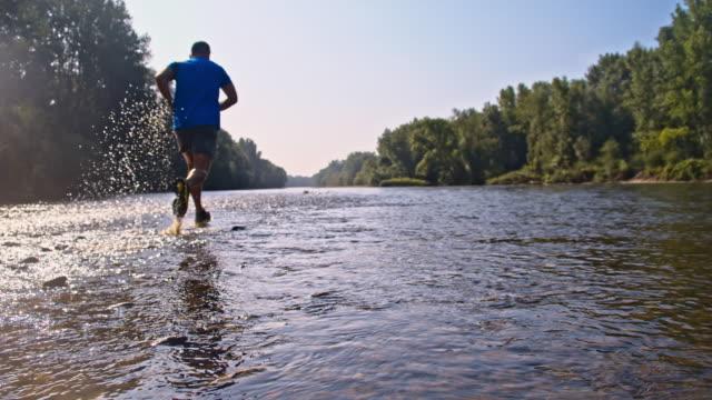 vidéos et rushes de slo missouri extrême courir dans les eaux peu profondes - endurance