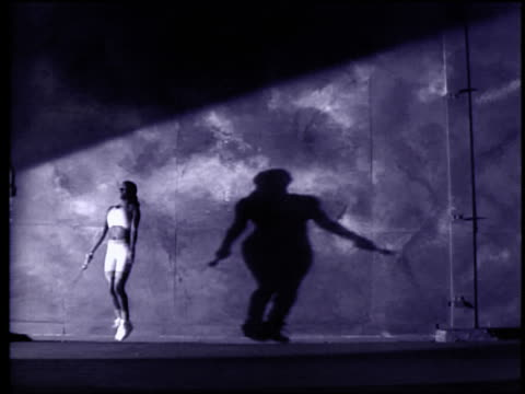 b/w extreme slow motion black woman jumping rope against red wall - viraggio video stock e b–roll
