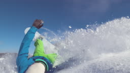 SLOW MOTION, CLOSE UP: Extreme snowboarder crashes into untouched powder snow.