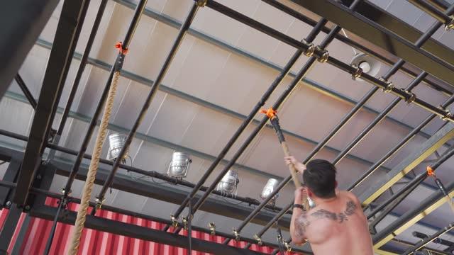 vídeos y material grabado en eventos de stock de deporte extremo asiático chino macho atleta masculino de escalada de cuerda en el gimnasio - entrenamiento sin material