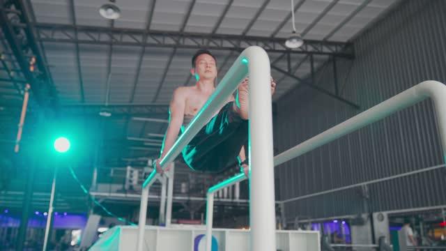 vídeos y material grabado en eventos de stock de deporte extremo asiático chino macho atleta masculino practicando calistenia en el gimnasio - entrenamiento sin material