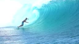 SLOW MOTION: Extreme surfer surfing inside big tube barrel wave