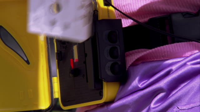 extreme tight shot of a woman placing a cassette in a walkman on a park bench. - stereo personale video stock e b–roll