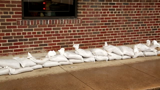 extreme weather. sandbags along sidewalk. rising water. rain storm. - sandbag stock videos and b-roll footage