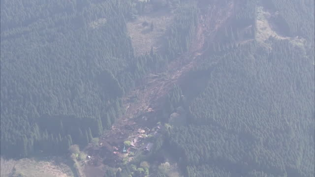 Extreme wide angle view of huge landslide occurred in Minami Aso Village after intense earthquakes hit Kumamoto area Zooming in on the rescuers and...