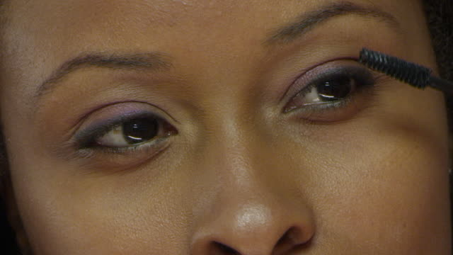 extreme cu young woman's eyes as she applies mascara in front of bathroom mirror - extreme close up stock videos & royalty-free footage