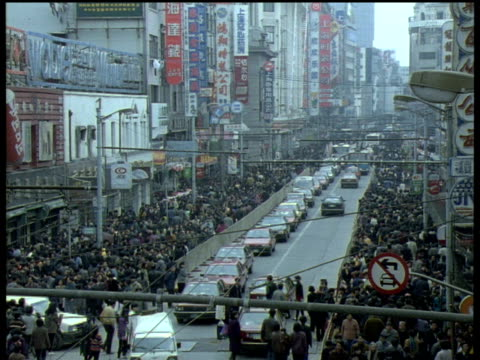 extremely busy street with chinese signs on either side. pavements filled with people as cars move down road shanghai - 1994 stock-videos und b-roll-filmmaterial