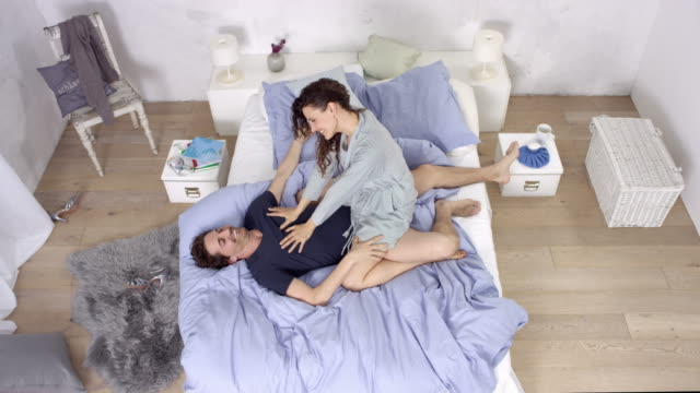 extremely good looking love couple having a good time in bed during day